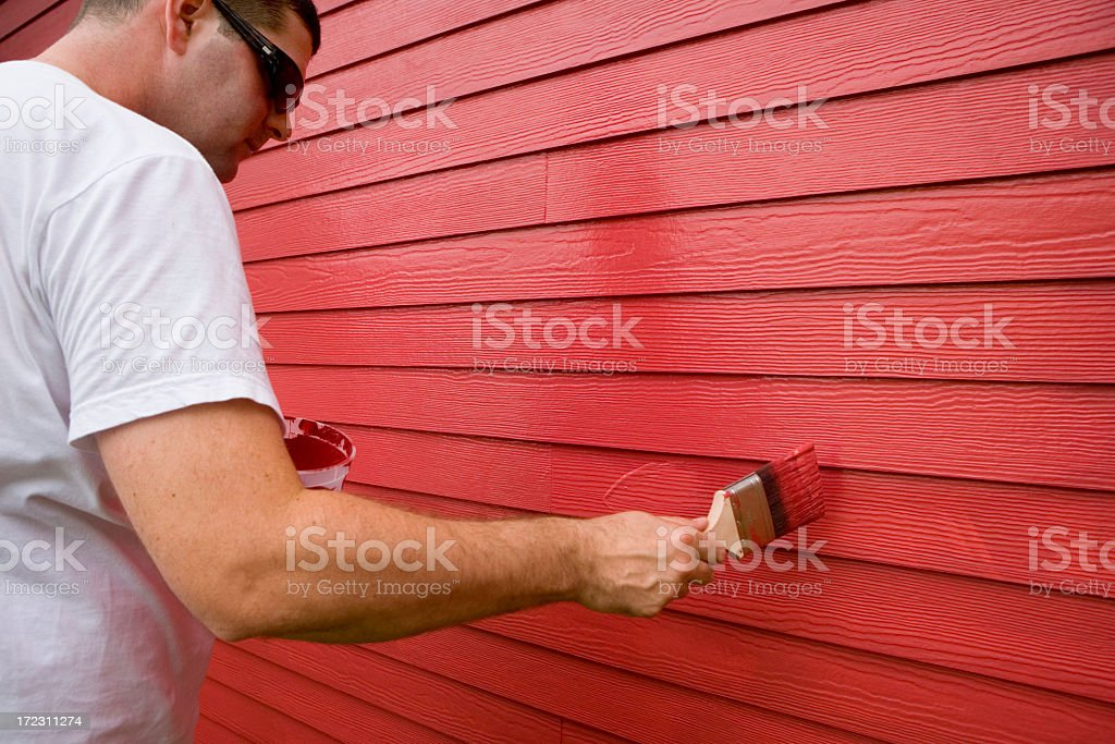 Man painting wood exterior with red paint royalty-free stock photo