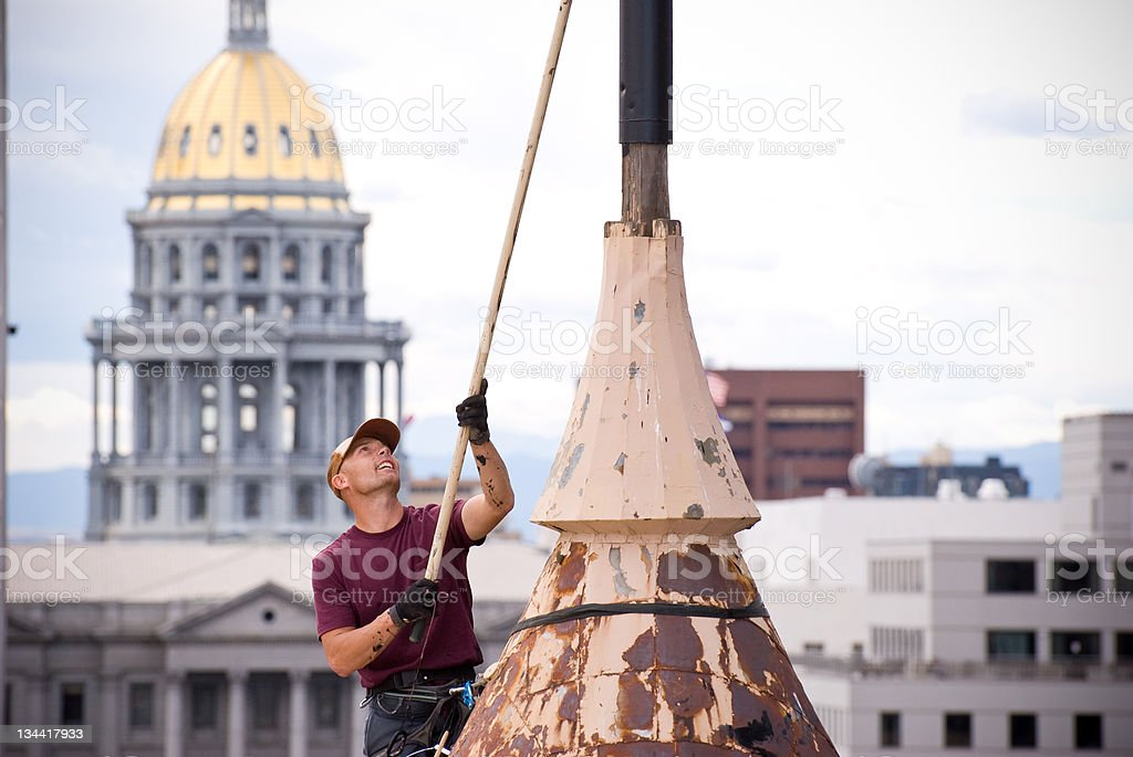 Man Paints Flagpole on Building Next To State Capitol Denver royalty-free stock photo