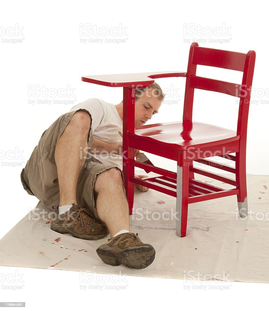 Man Paints Red Over Primer on Furniture (Desk Restoration Series) stock photo