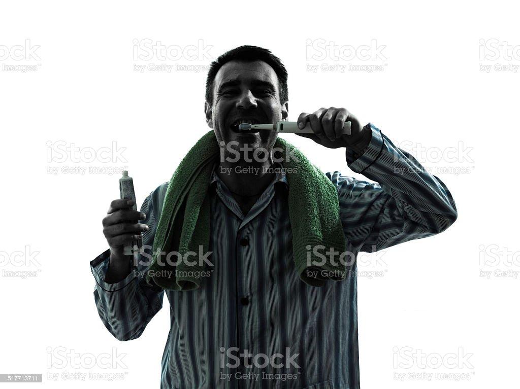 man pajamas tooth brushing silhouettes stock photo