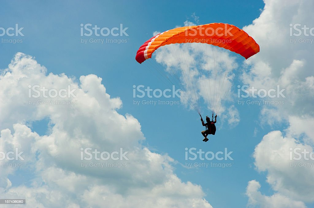 A man paragliding in the blue sky stock photo