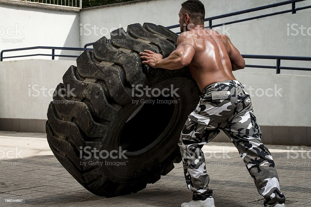 Man participating in a gym workout doing tire flip stock photo