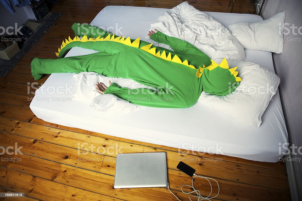 Man Passed Out Morning After Late Night in Dinosaur Costume stock photo