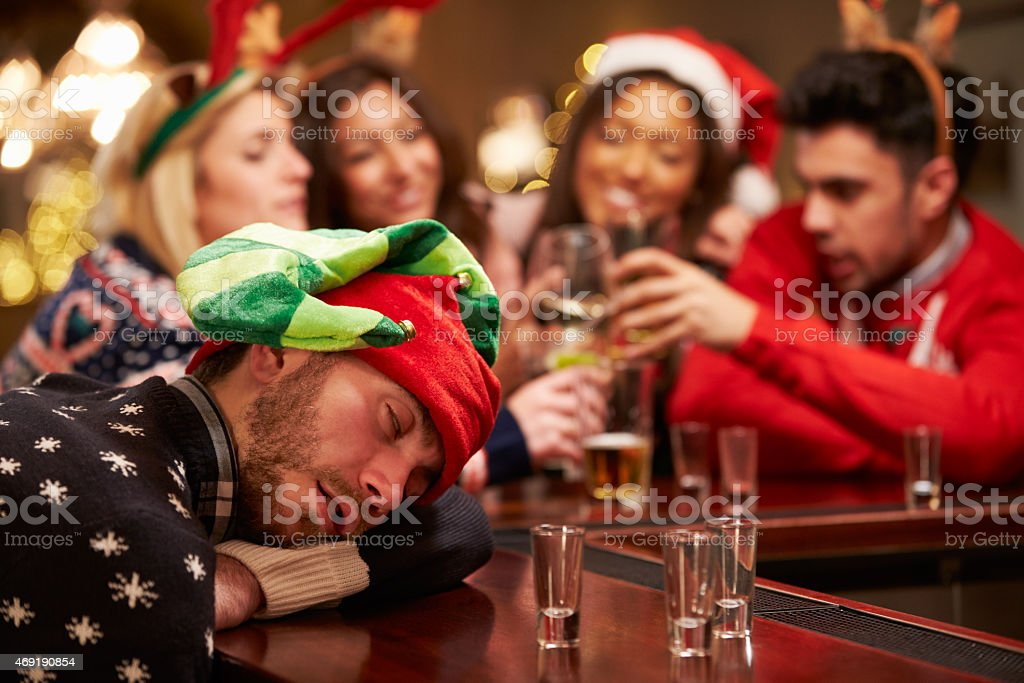 Man Passed Out On Bar During Christmas Drinks With Friends stock photo