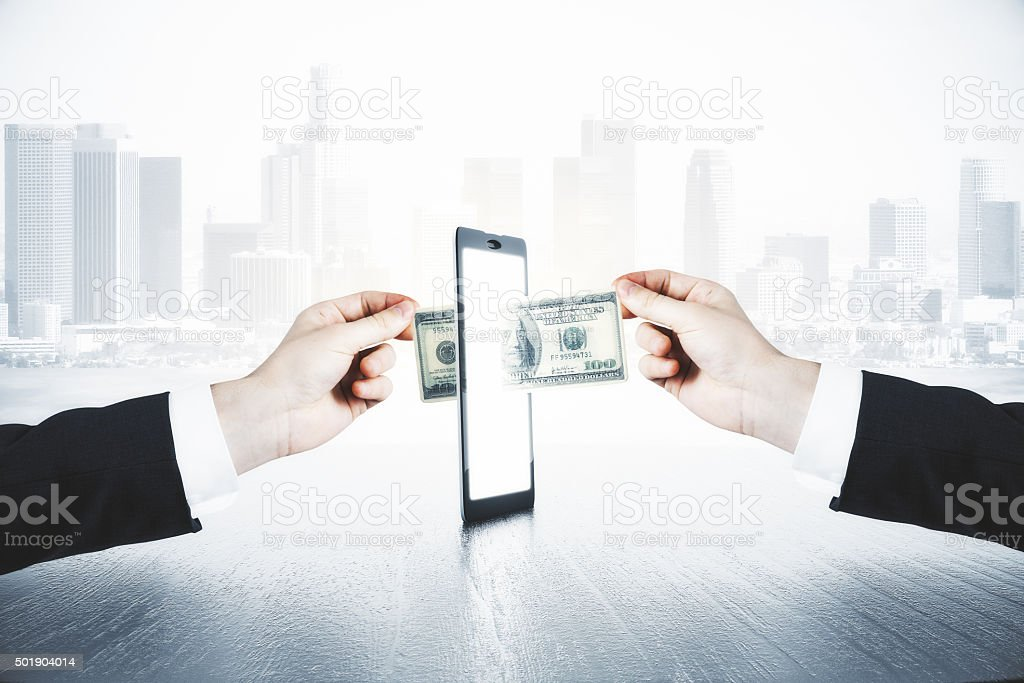 man passes another man money through smartphone stock photo