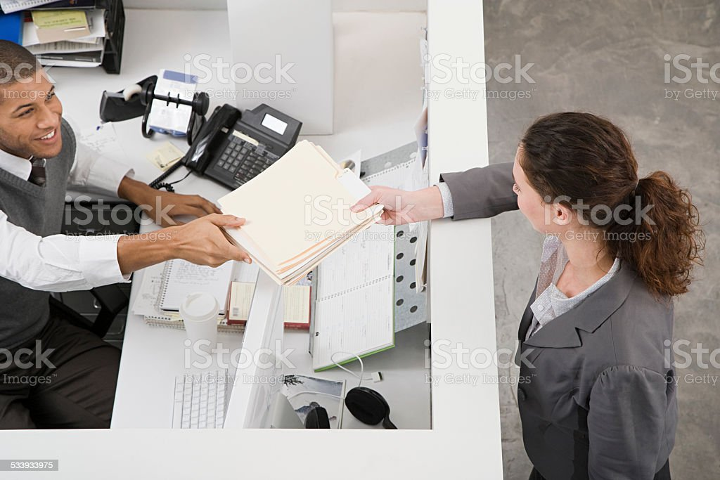 Man passing file to colleague stock photo
