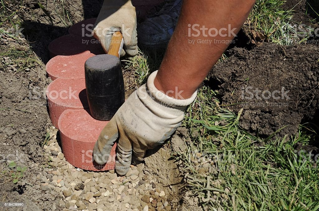 Man paving using red crescent shaped cobblestones. stock photo