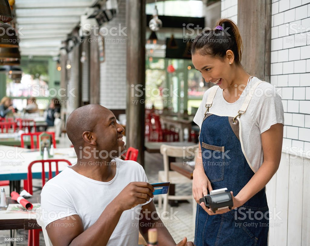 Man paying by card at a restaurant stock photo