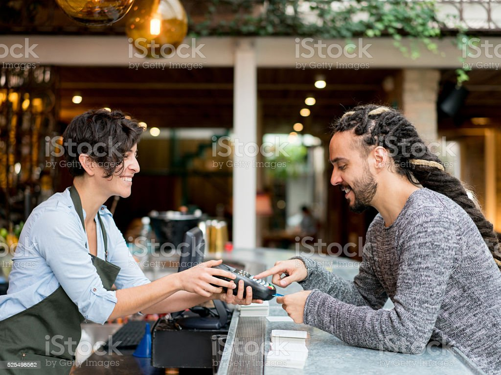 Man paying by credit card at a restaurant stock photo
