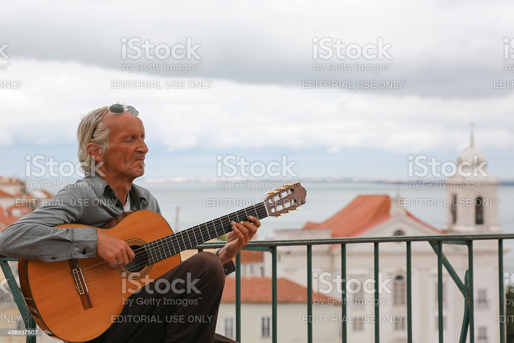 Man Paying Guitar for Tourist in Lisbon, Portugal royalty-free stock photo