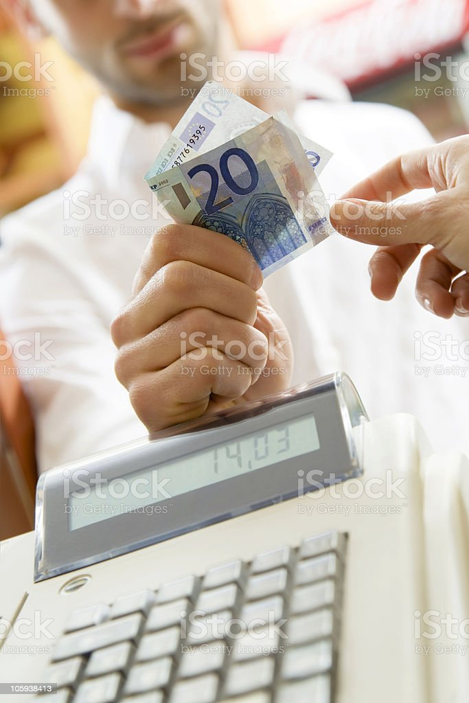 Man paying in 20 currency with a 14.03 bill stock photo