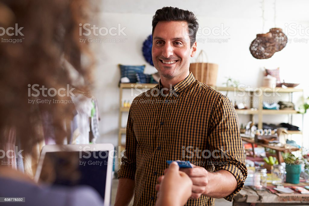 Man paying sales assistant with credit card in clothes shop stock photo