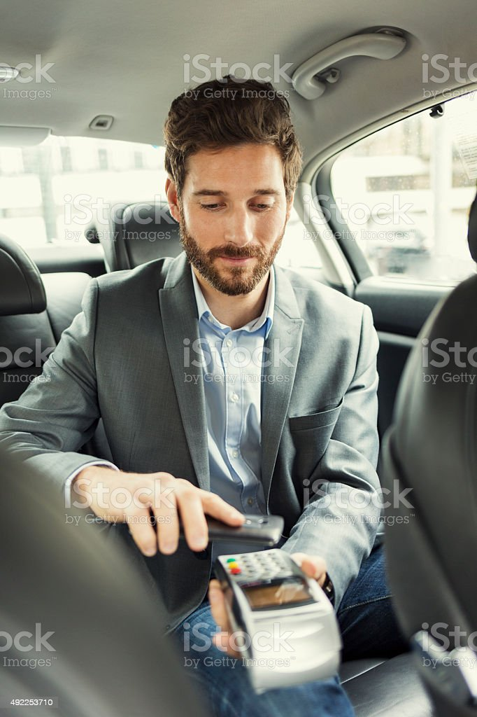 Man paying the taxi with the mobile phone. NFC technology stock photo