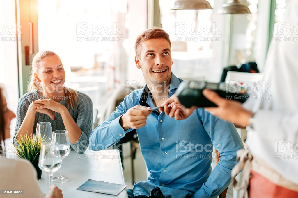 Man Paying Their Lunch With Credit Card In Restaurant. stock photo