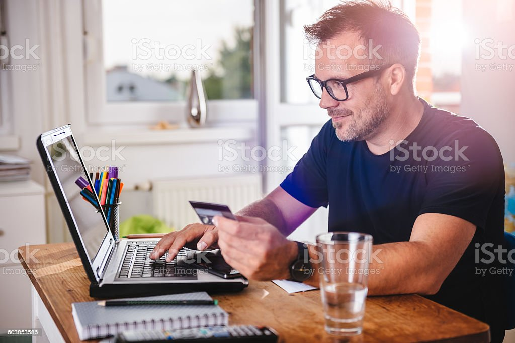 Man paying with credit card on laptop stock photo