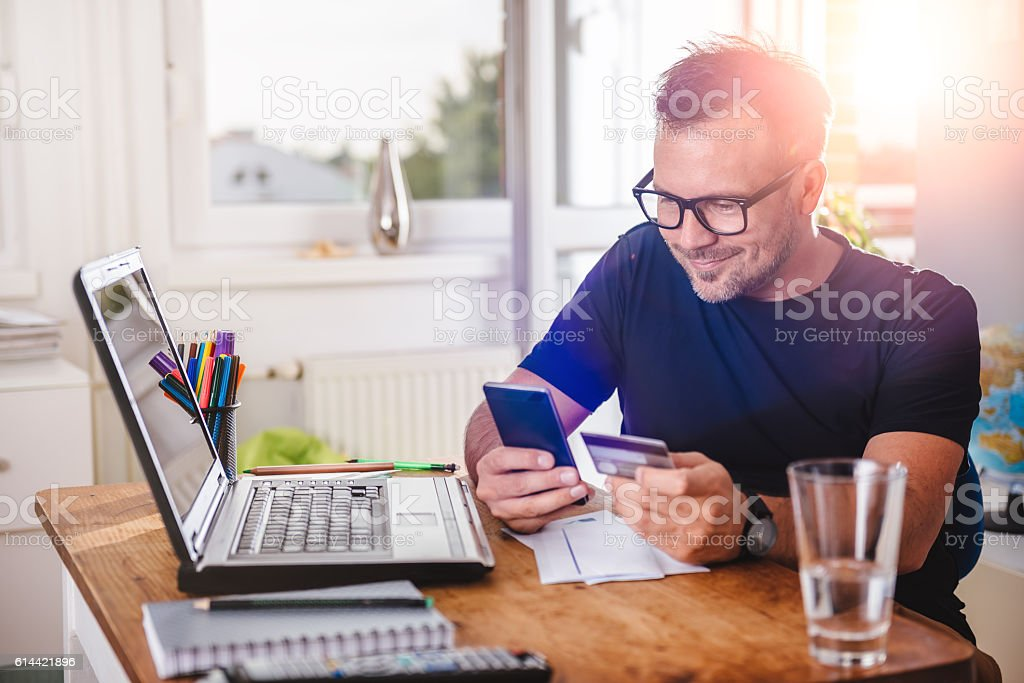 Man paying with credit card on smart phone stock photo