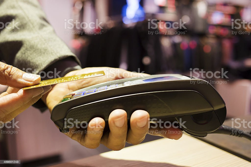 Man paying with NFC technology on credit card, clothing store stock photo