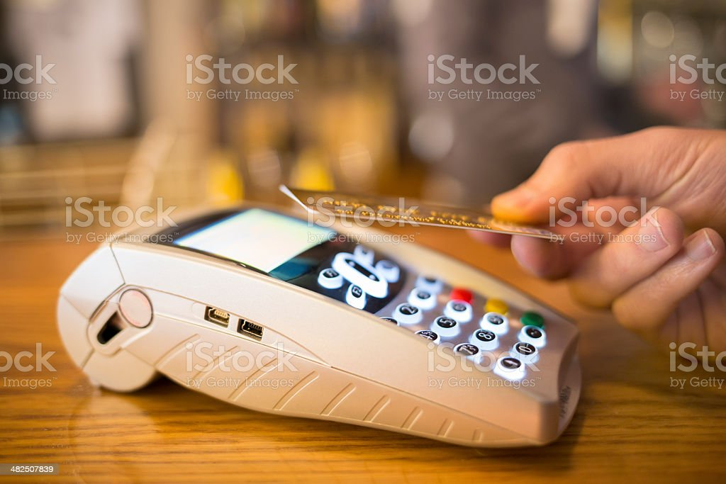 Man paying with NFC technology on credit card, restaurant, shop stock photo
