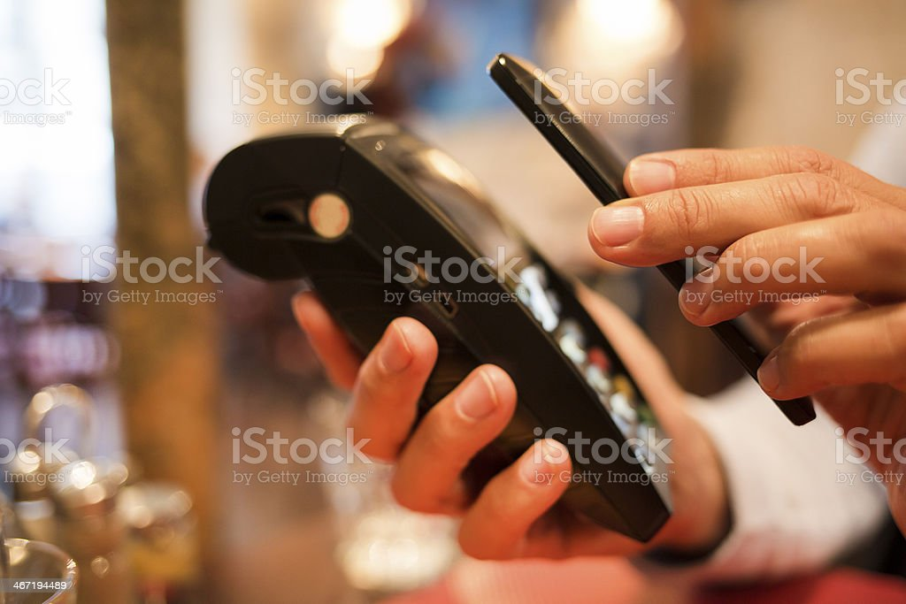 Man paying with NFC technology on mobile phone, in restaurant stock photo
