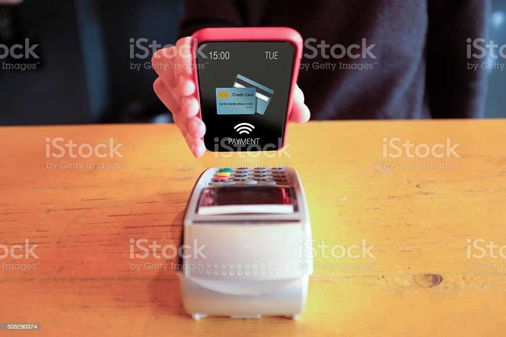 Man Paying With NFC Technology On Smart Phone stock photo