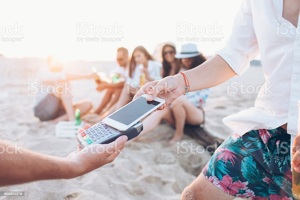 Man paying with smart phone on beach stock photo