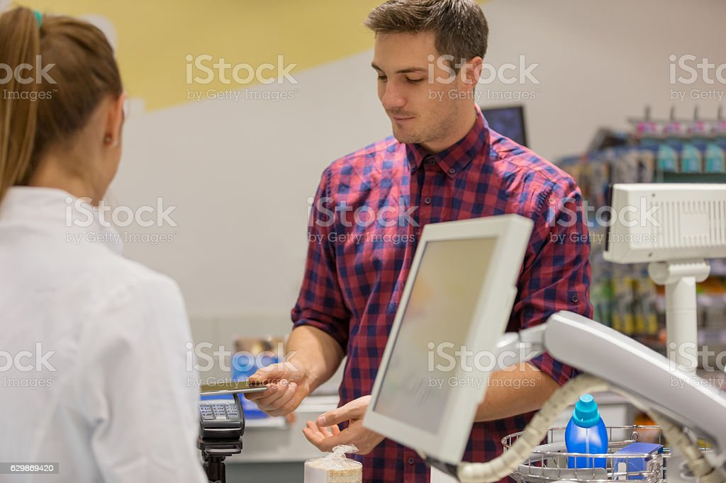 Man paying with smartphone in supermarket stock photo