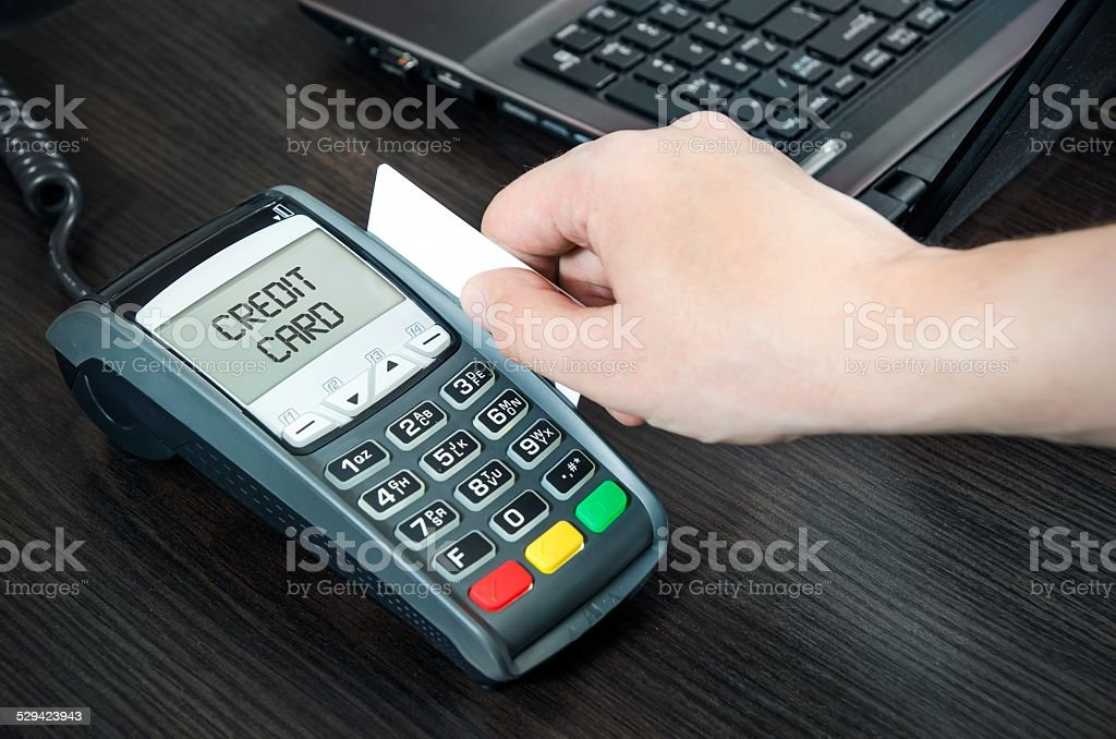 Man pays with credit card. Swiping plastic card through terminal stock photo
