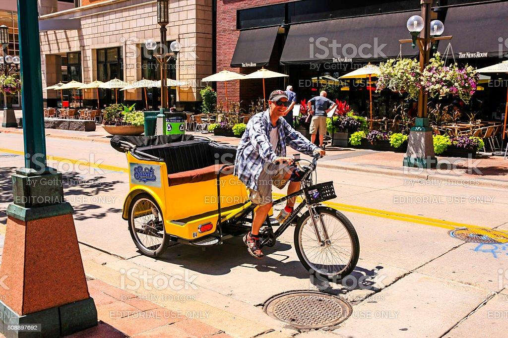 Man peddling a yellow trishaw taxi in downtown Minneapolis MN stock photo