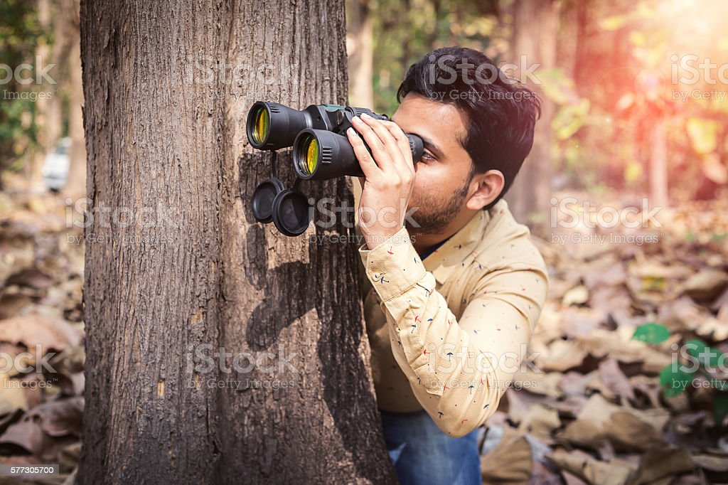 Man peeking from behind a tree in forest with binoculars. stock photo