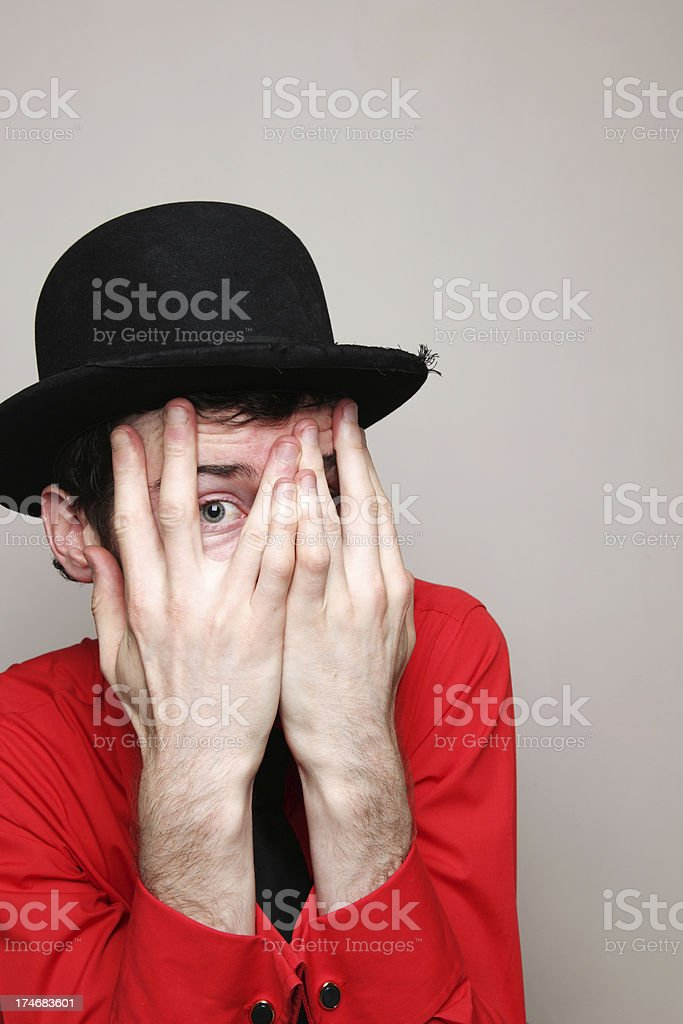 man peeking through his fingers with a bowler hat on royalty-free stock photo