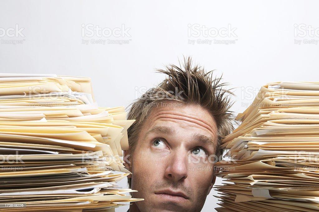 Man Peeking Up Between Stacks of Paperwork stock photo