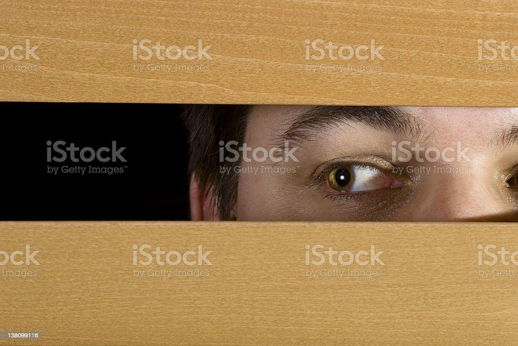 Man peeks through the blinds stock photo