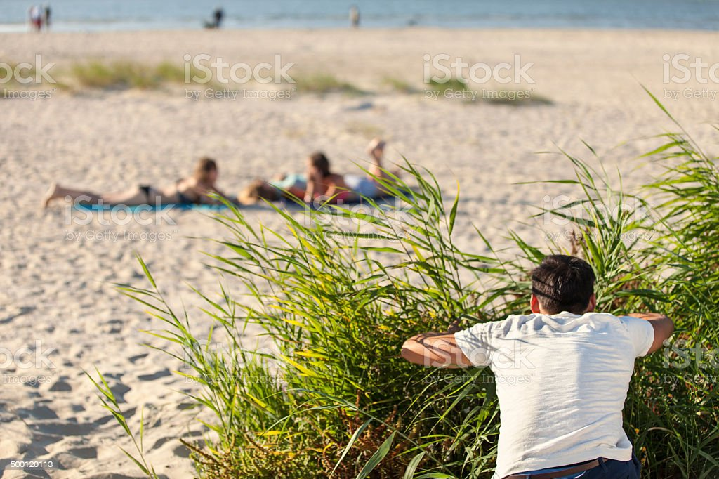 Man Peeping At Women On Beach stock photo