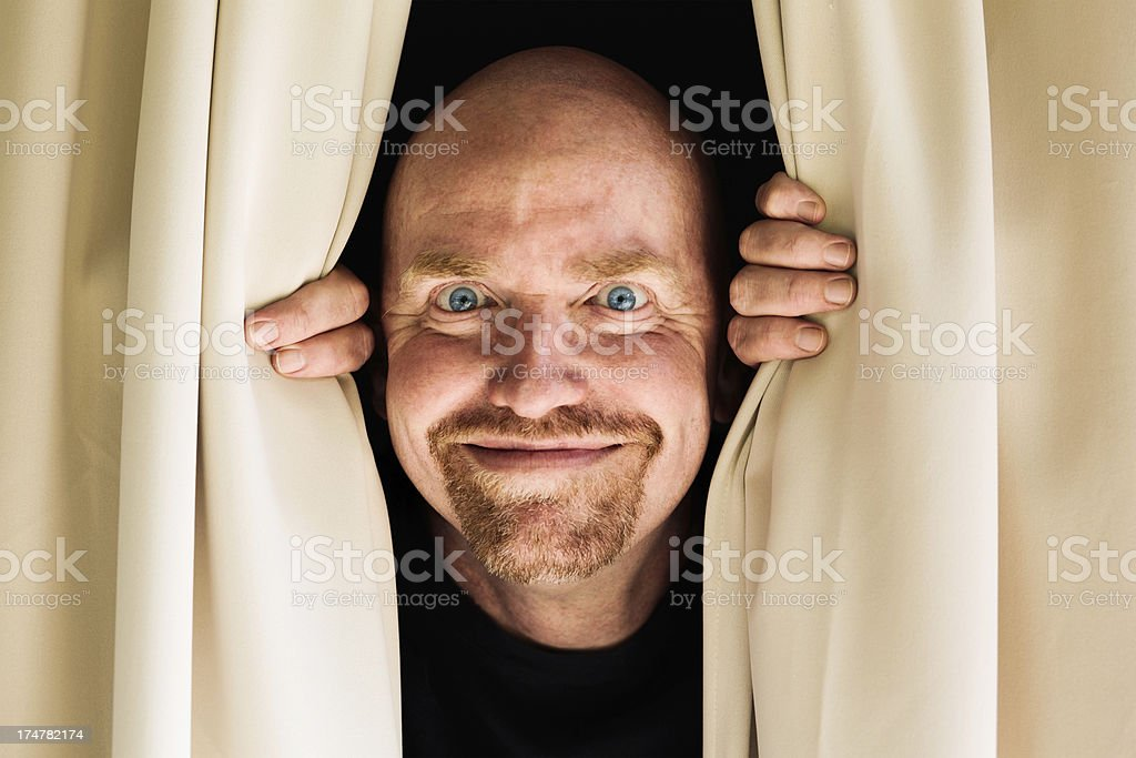 Man peeps through curtains with a beaming smile - surprise! stock photo