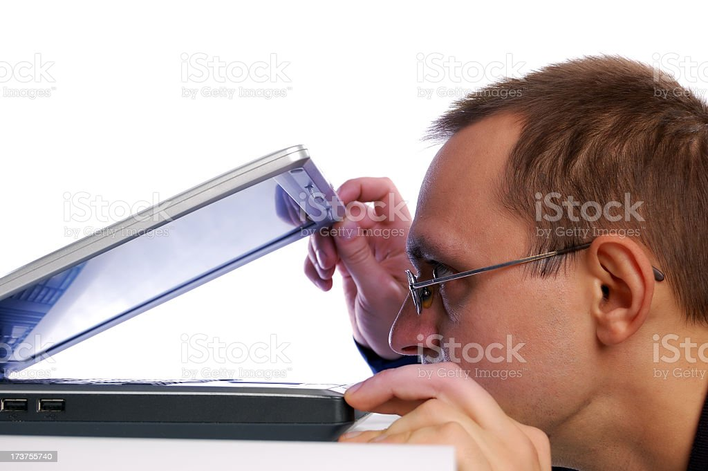 A man peering into an almost closed laptop royalty-free stock photo