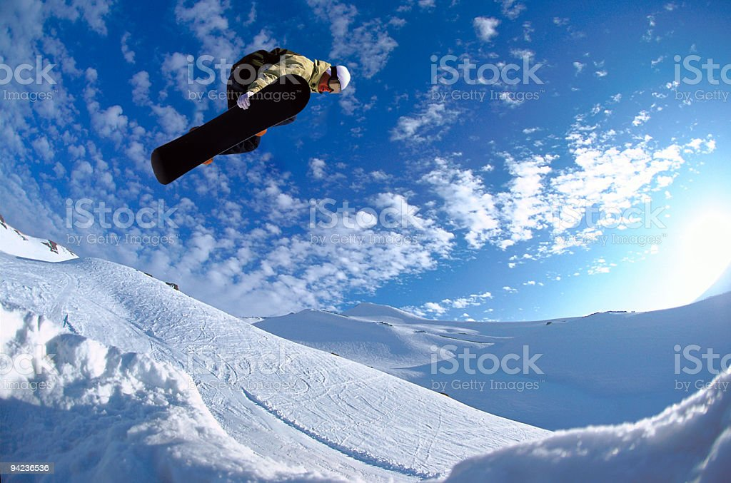 Man performing a snowboard jump stock photo