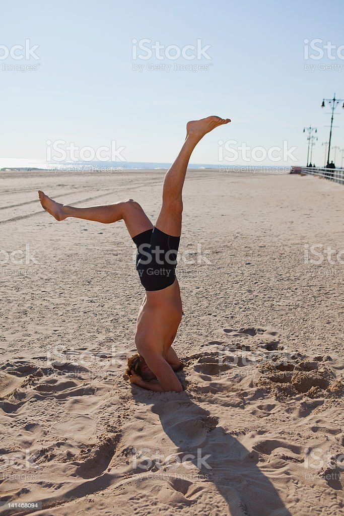 Man performing headstand on a beach stock photo