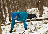 Man performs exercise in the winter woods.