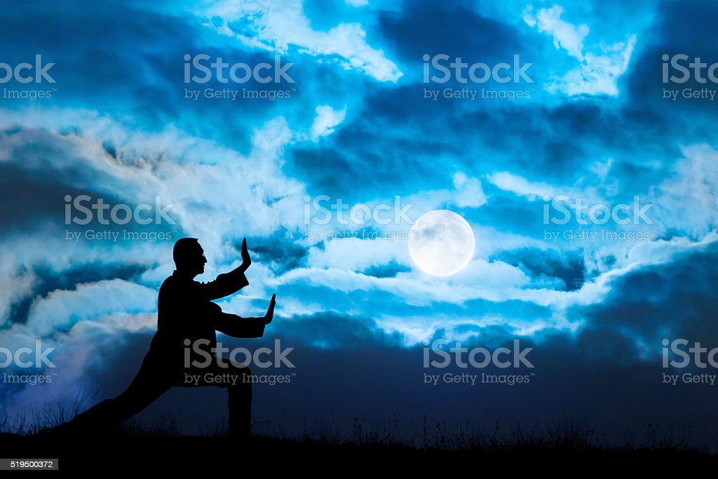 Man performs Tai Chi sport under moonlight stock photo