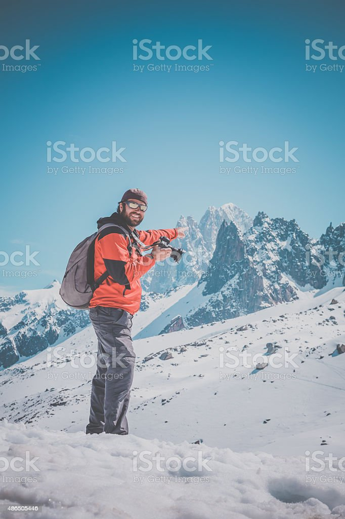 Man Photographer Taking Picture with DSLR Camera of Mountains stock photo