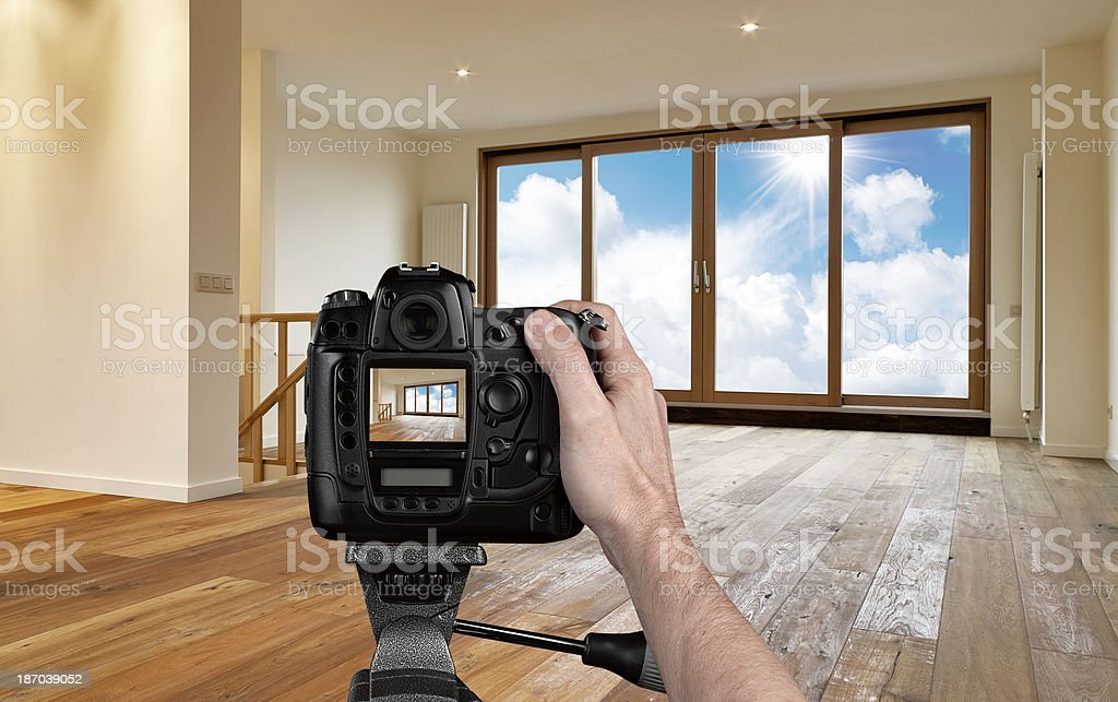 Man photographing empty living room with digital camera stock photo
