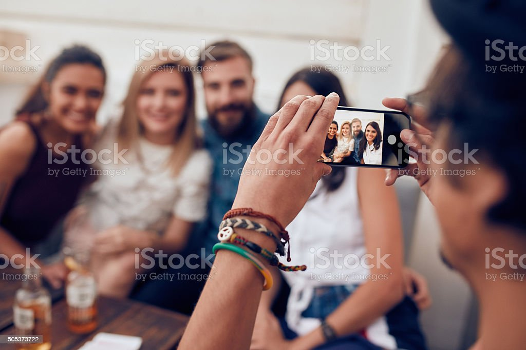 Man photographing his friends at party stock photo
