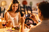 Man photographing his girlfriend with smart phone in the restaurant.