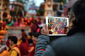 Man photographing holi ceremony with tablet in Parmarth Niketan ashram