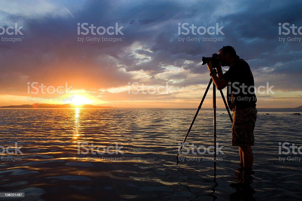 Man Photographing in Water at Sunset stock photo