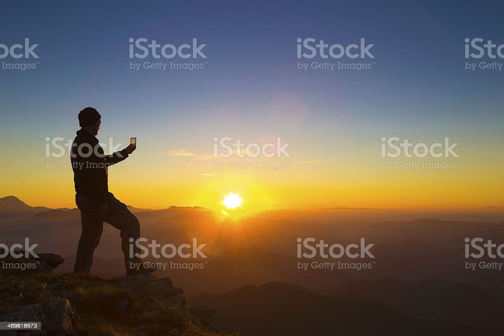 Man photographing sunset on a Mountain top stock photo