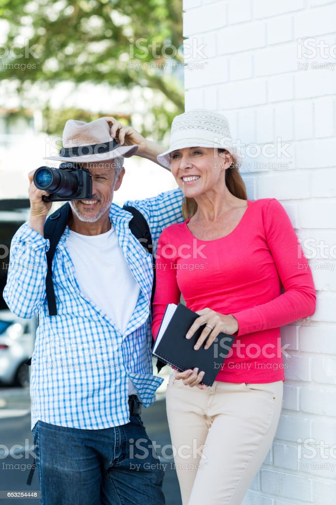 Man photographing while standing by wife stock photo
