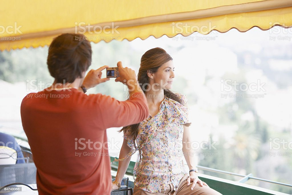 Man photographing woman in outdoor cafe royalty-free stock photo