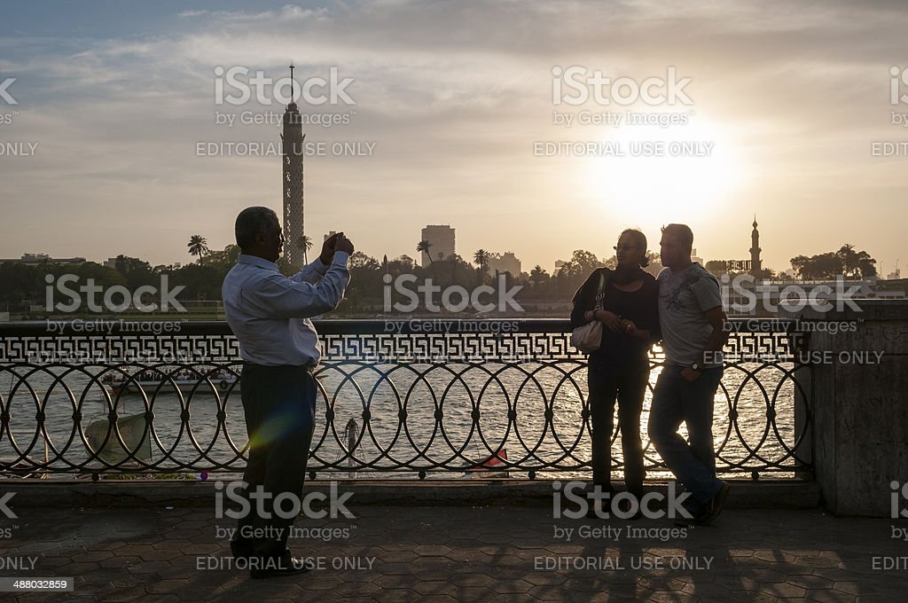 Man photographs two people beside Nile River in Cairo, Egypt stock photo