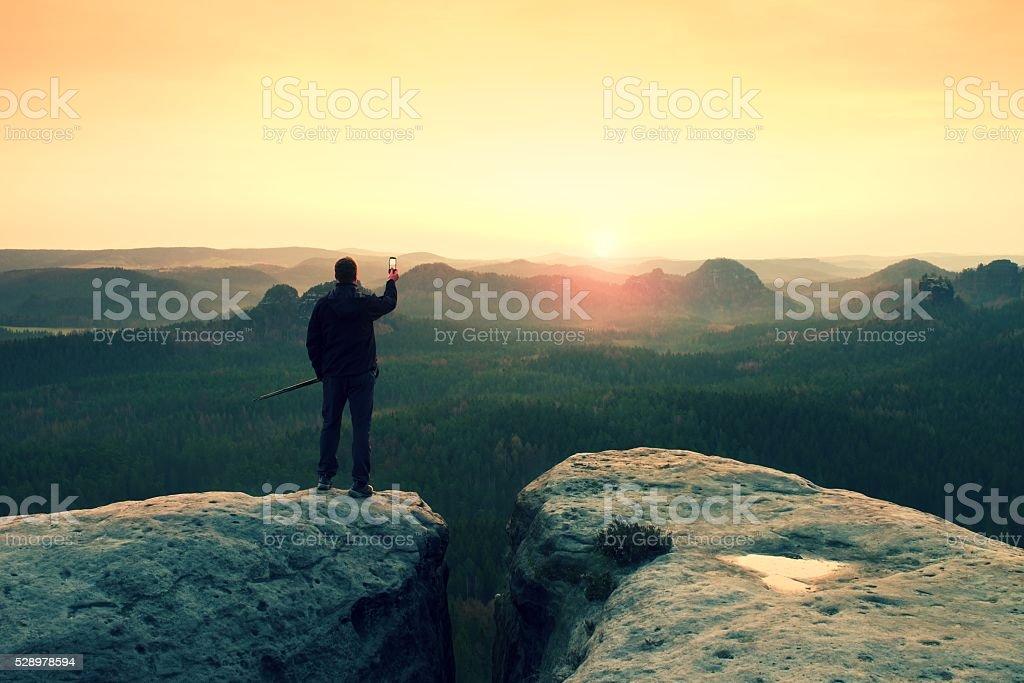 Man photography on peak of rock empire. Dreamy spring  landscape stock photo